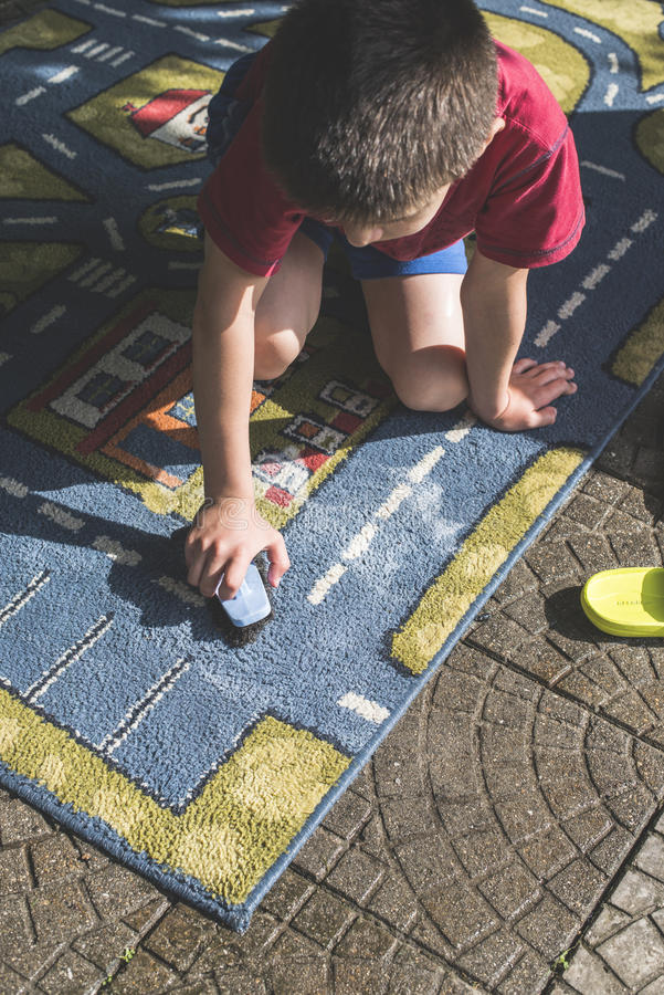 Child clean a carpet. Child clean carpet. Exterior shot royalty free stock photos