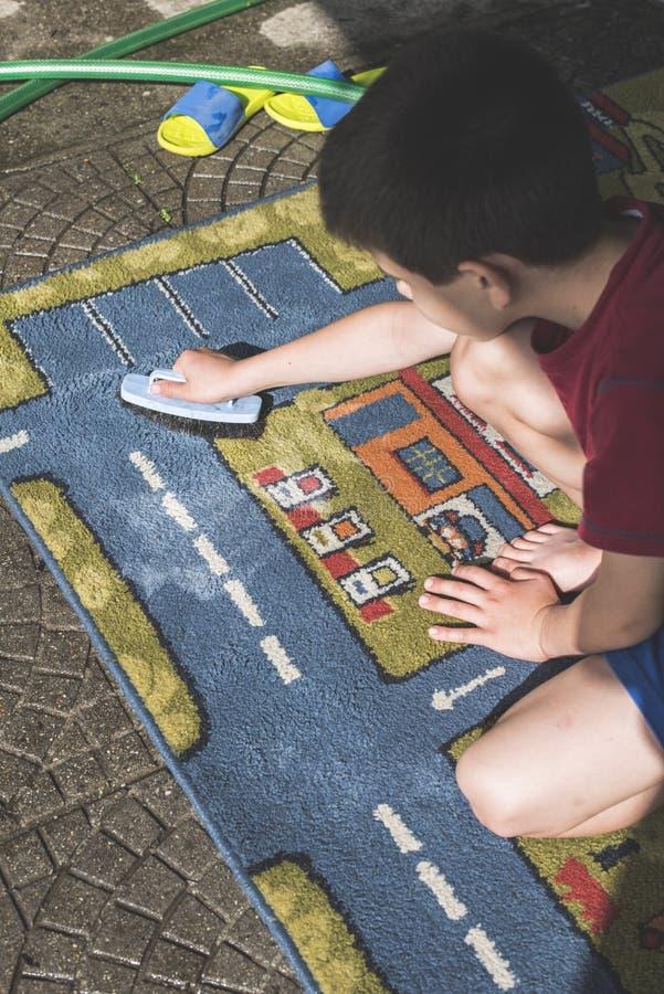 Child clean a carpet. Child clean carpet. Exterior shot stock photo