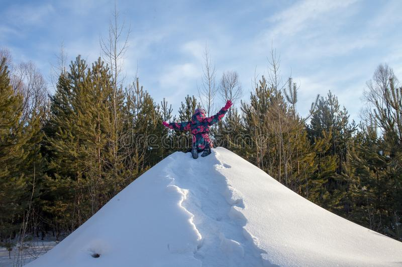 Child climb the hill with a tube for descent. Children ski in the winter with a slide on the tubing. kid runs to hill and sledding royalty free stock image