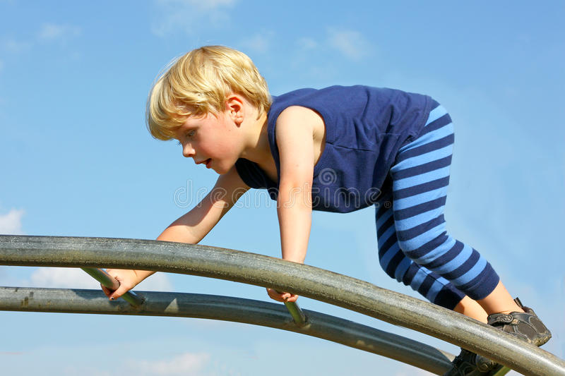 Child Climbing Ladder at Playground. A cute little boy is carefully climbing a ladder toy at the playground on a summer day royalty free stock photography