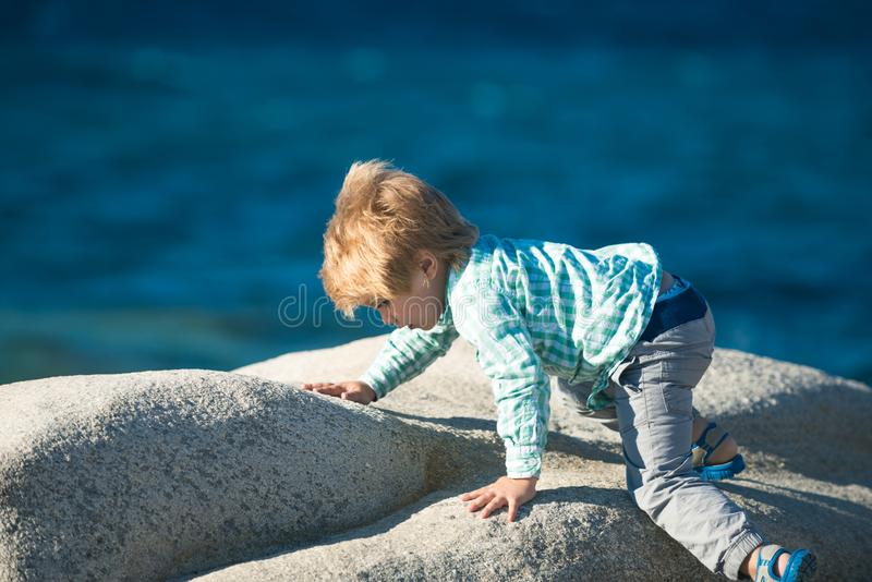 Child climbing stone. Cute fashionable baby boy in blue shirt and gray pants climbs on stone at sunny summer day on stock photos
