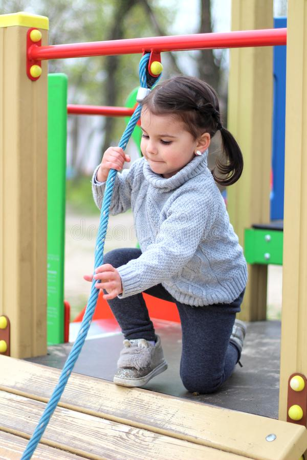 a child is climbing a tightrope in the playground stock image