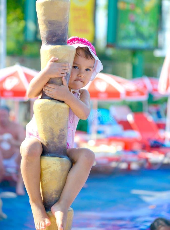 Child climbing a tree. fake palm at aqua park royalty free stock photography