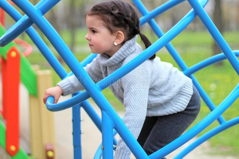 the child climbs the blue welded construction of pipes in the playground royalty free stock photo
