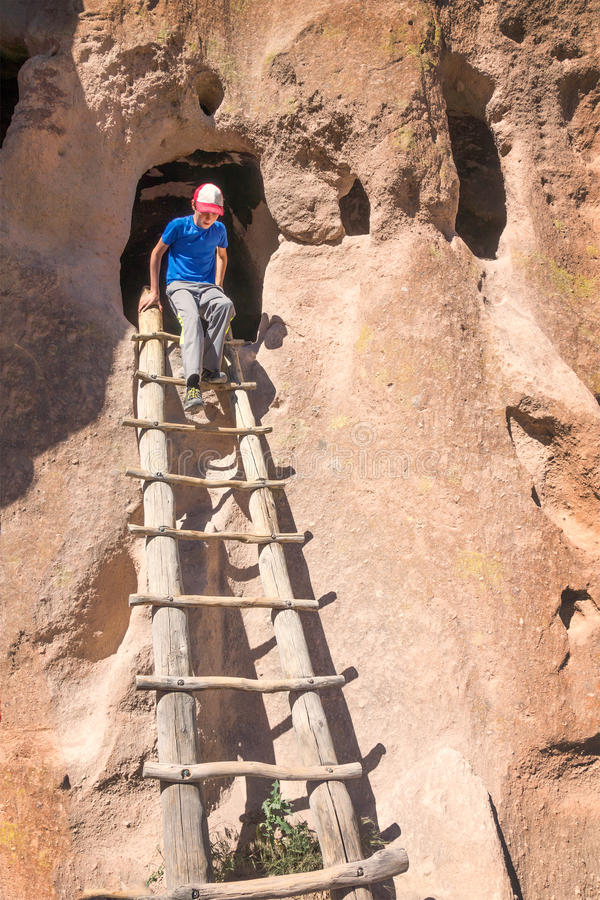 Child climbs the ladder out of Cavate, called Cave Kiva. Bandel stock photo