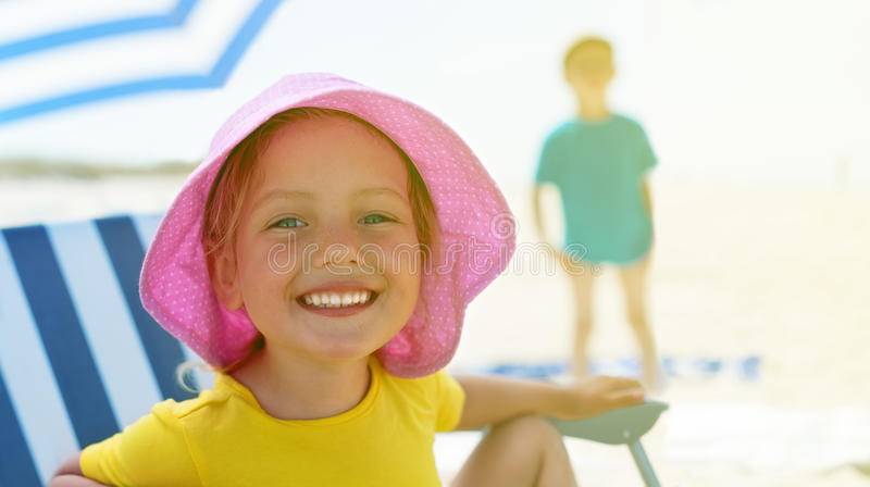 Child close up portrait happy smile summer camp sitting chair umbrella. Selective focus backlight stock photo