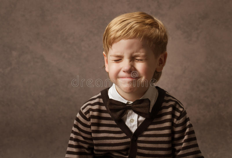 Child with closed eyes. Boy in brown retro bow tie. Child happy portrait with closed eyes. Boy in brown retro bow tie waiting surprise royalty free stock images