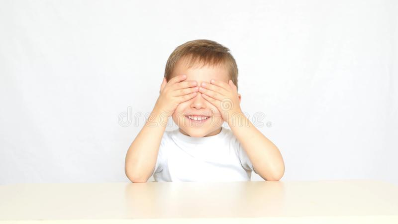 The child closes his eyes with his hands in anticipation of delicious potato chips - 2. The child is served a plate with. The child closes his eyes with his royalty free stock image