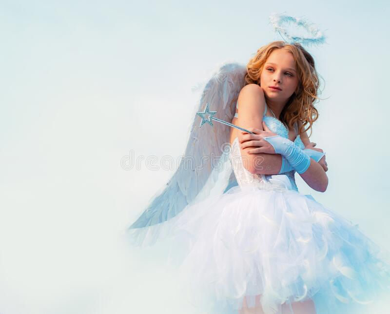 A child in the clothes of an angel on sky background - Valentine concept. Child with angelic character. Little angel royalty free stock images