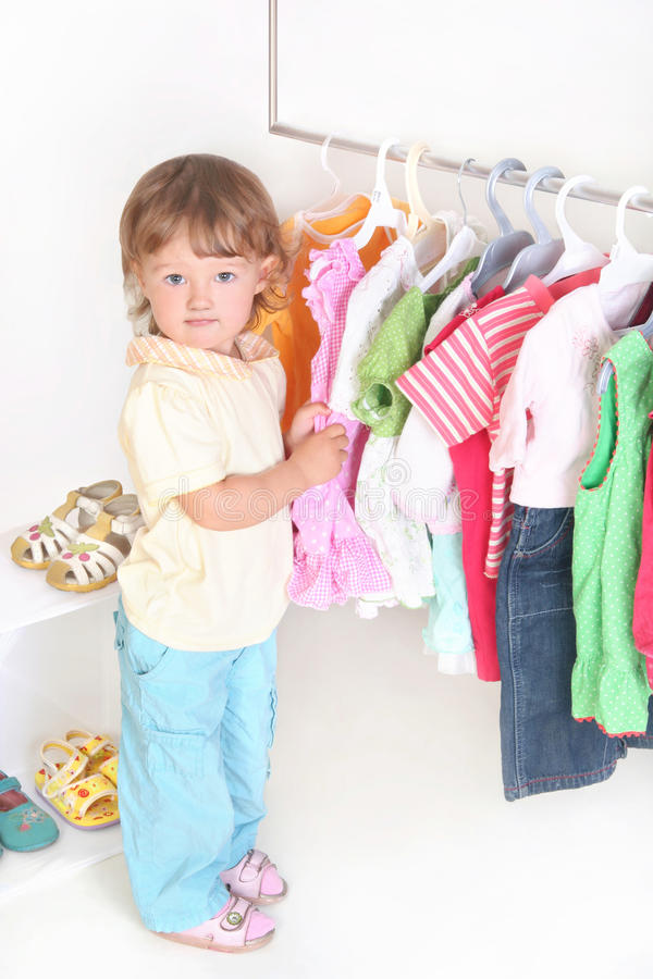 Child in the clothes shop. Want to buy new dress stock photography