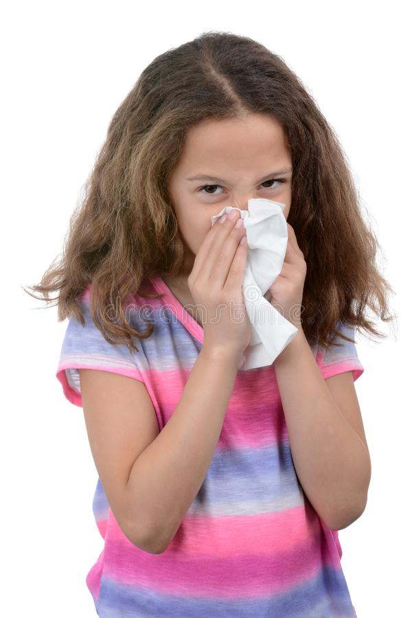 Child with a cold blowing nose. Young girl blowing her nose with tissue health concept white background stock images