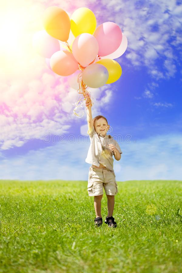A child with colorful balloons. Happy kid on his birthday on green grass. Positive toddler. Baby Outdoors stock photography