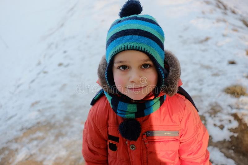 The child in a colorful hat stands on the snow royalty free stock images