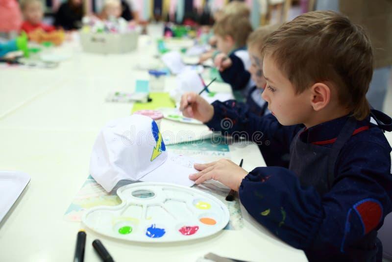Child coloring baseball cap. Child coloring a baseball cap at table royalty free stock photo