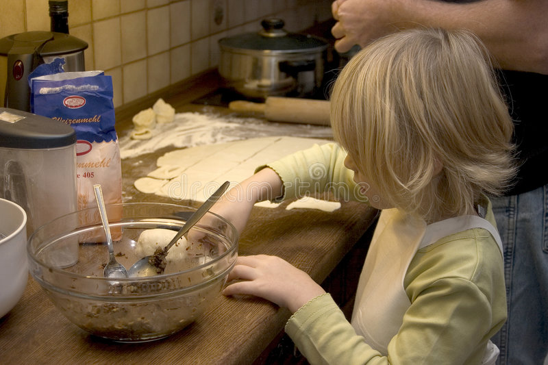 Child cooking. Child in the kitchen cooking Tortellini stock photography