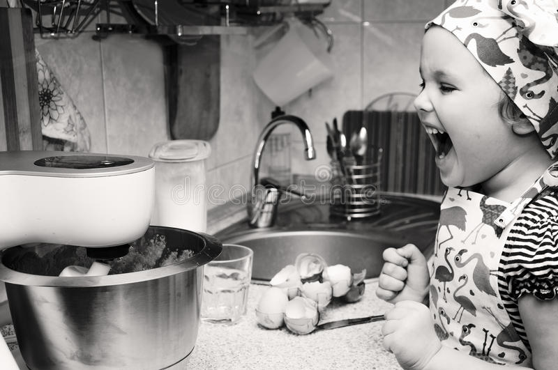 Child cooking at home. Black and white photo. Child cooking at home sweet pie, mixes ingredients. Black and white photo stock image