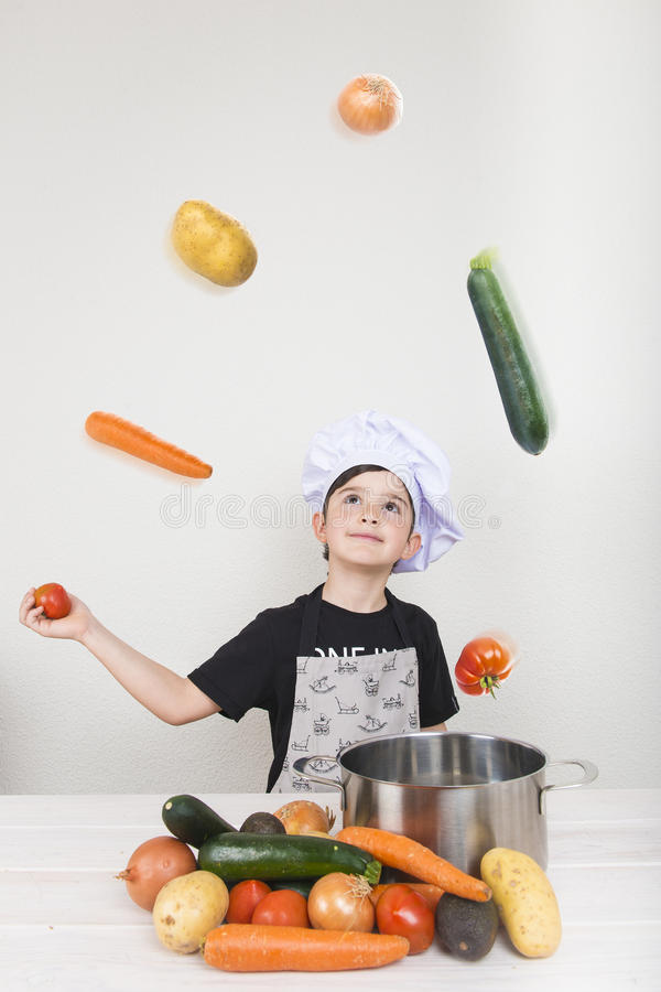 Child cooking with vegetables royalty free stock photography
