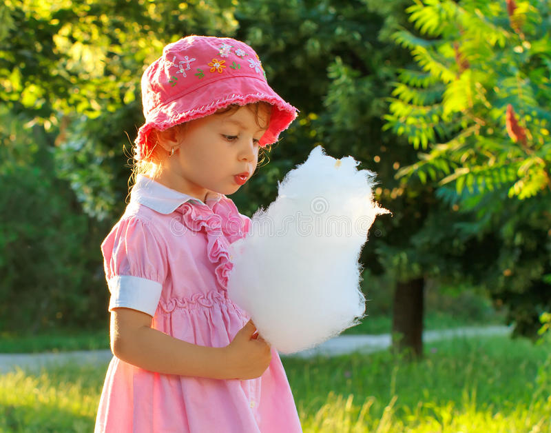 Child with cotton candy. Little girl eating cotton candy in park stock image