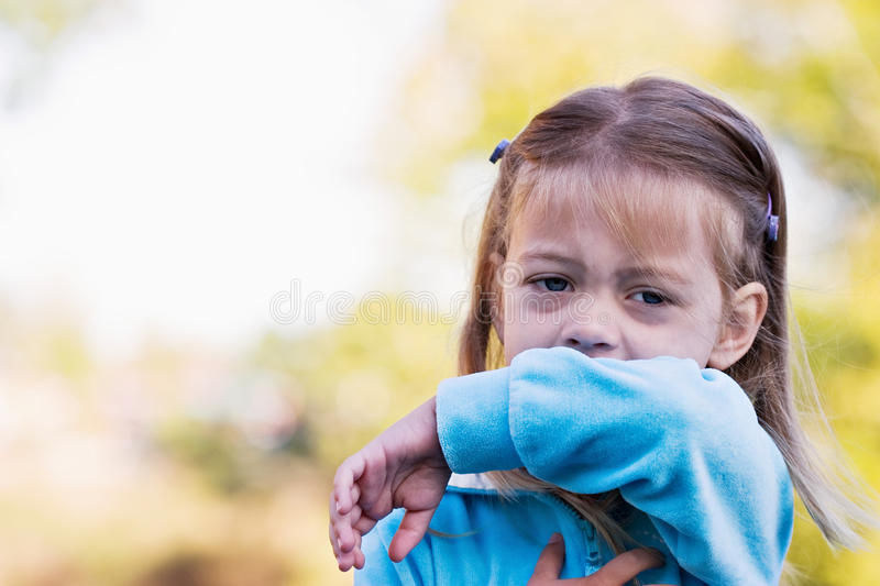 Child coughing or sneezing into arm royalty free stock photography