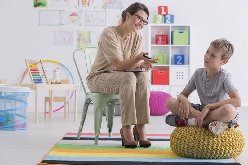Child counselor during successful therapy. Professional child counselor during successful therapy session with little boy sitting on pouf in office room royalty free stock photos