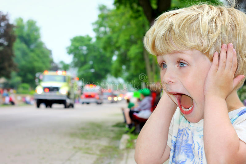 Child Covering Ears at Loud Parade stock images