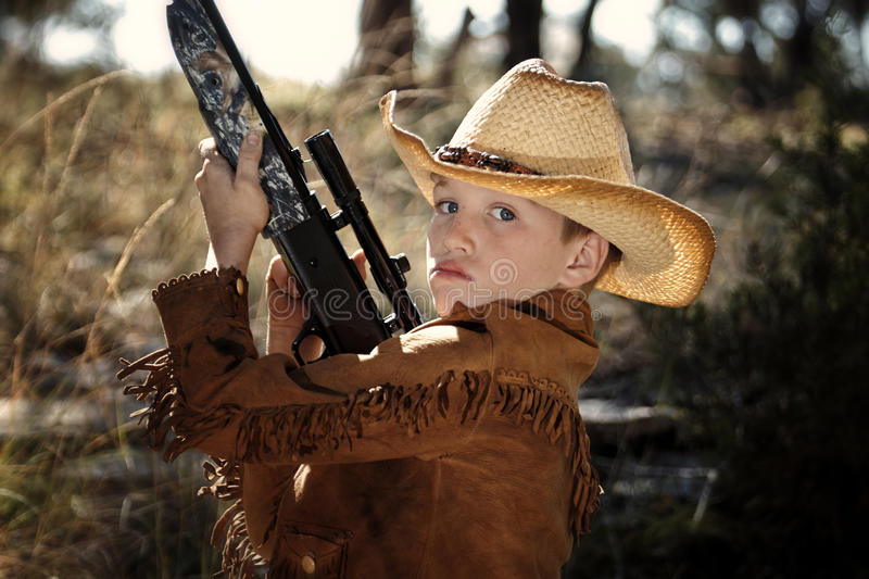 Child in cowboy outfit. A boy in a cowboy outfit with a rifle stock photography