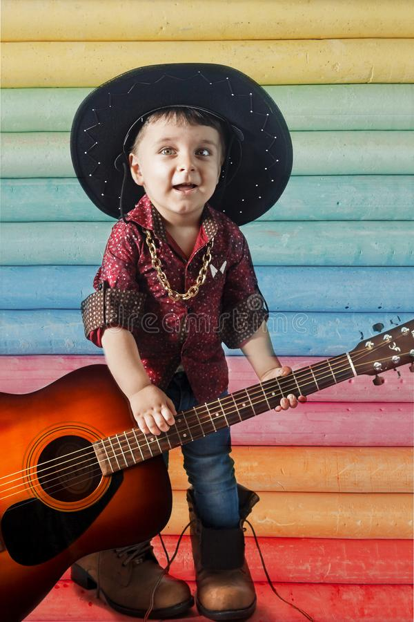 A child in a cowboy`s hat on a colored background playing the guitar royalty free stock images