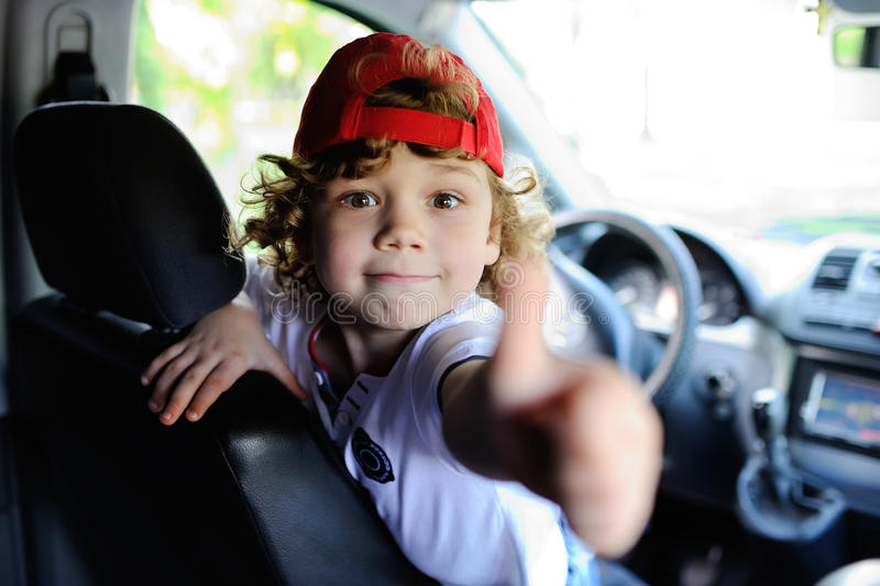 Child with curly hair and a red cap sits behind the wheel of car. Child with curly hair and a red cap sits behind the wheel of a car. baby boy grimaces in car stock images