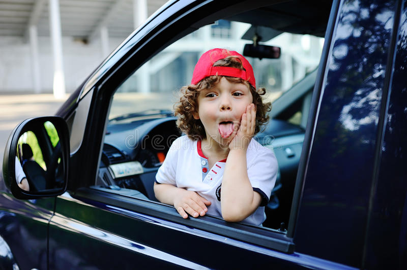 Child with curly hair and a red cap sits behind the wheel of car. Child with curly hair and a red cap sits behind the wheel of a car. baby boy grimaces in car royalty free stock photography