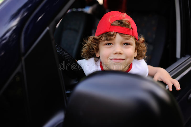 Child with curly hair and a red cap sits behind the wheel of car. Child with curly hair and a red cap sits behind the wheel of a car. baby boy grimaces in car royalty free stock images