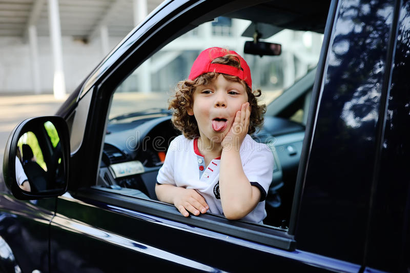 Child with curly hair and a red cap sits behind the wheel of car. Child with curly hair and a red cap sits behind the wheel of a car. baby boy grimaces in car royalty free stock image