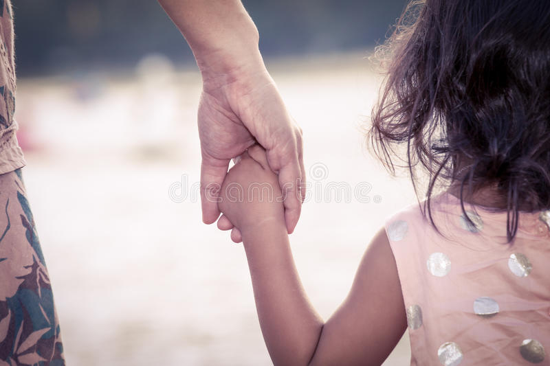 Child cute little girl and mother holding hand together stock image