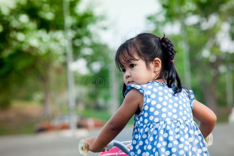 Child cute little girl riding bike stock photo