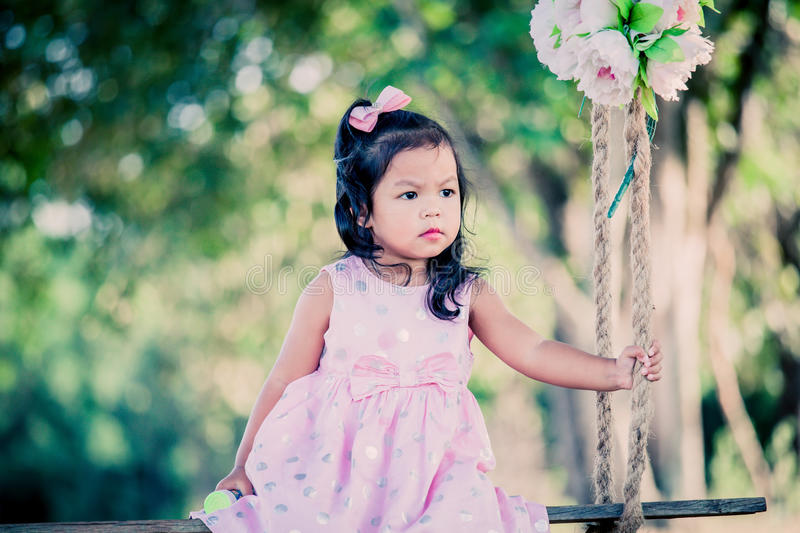 Child cute little girl sitting on swing in the park royalty free stock photography