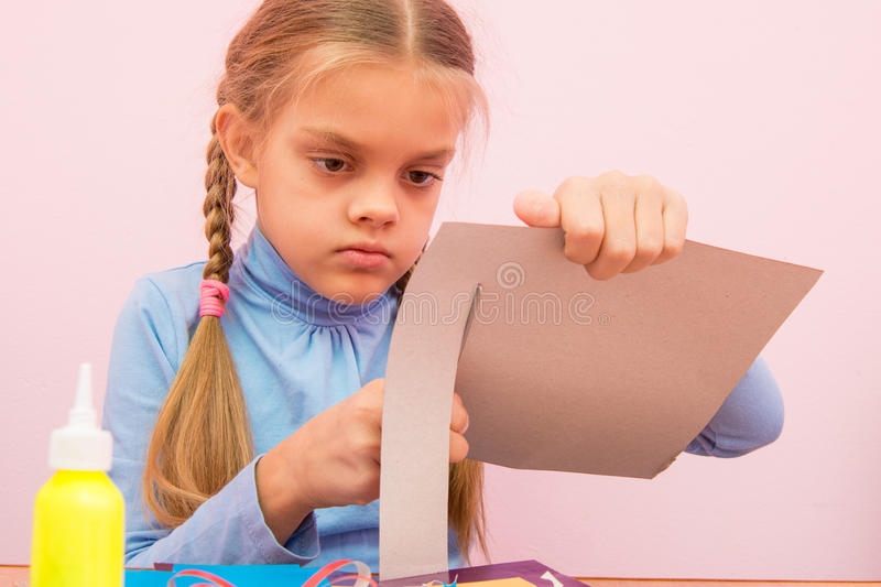 Child cuts a strip of cardboard in the classroom royalty free stock images