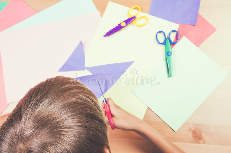 Child cutting colored paper with scissors at the table. Schoolboy cutting colored paper with scissors at the table stock images
