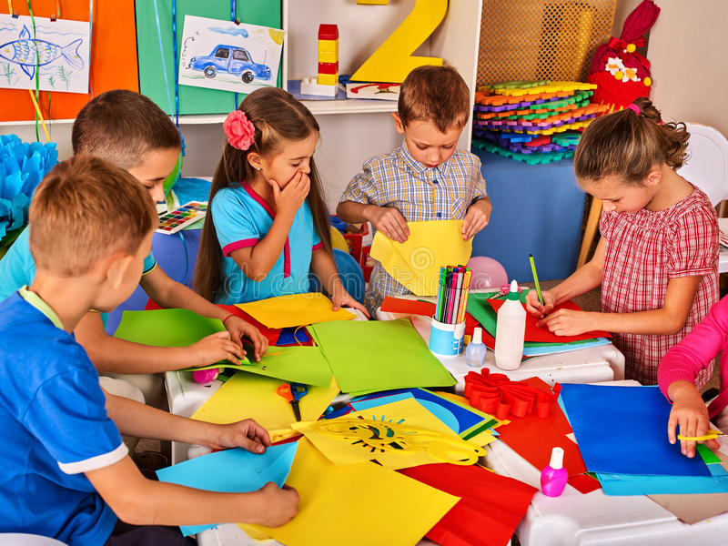 Child cutting paper in class. Development social lerning in school. royalty free stock image
