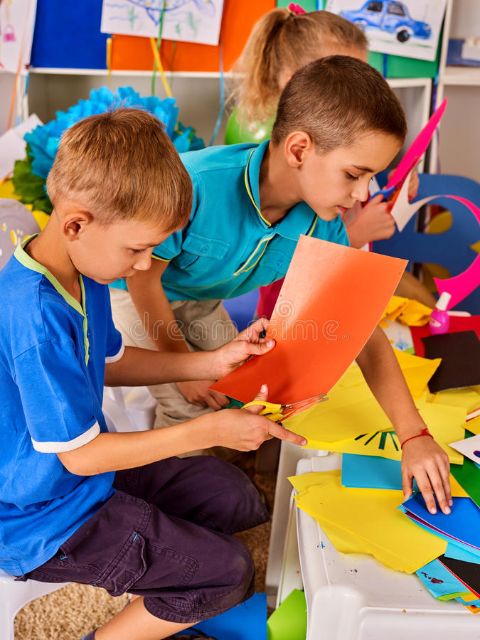 Child cutting paper in class. Development social lerning in school. stock photography