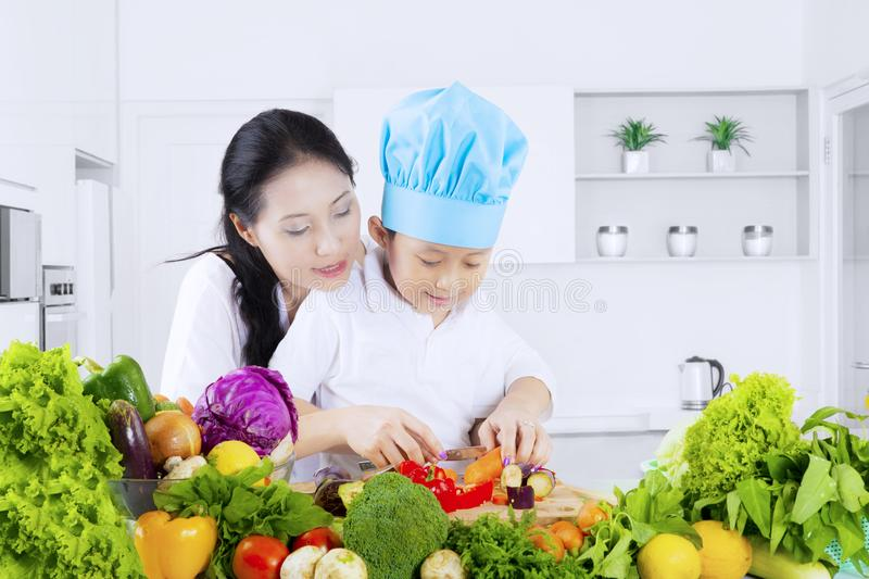 Child cutting vegetables with her mother royalty free stock photography