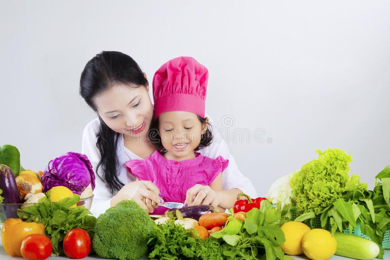 Child cutting vegetables with her mother royalty free stock photos