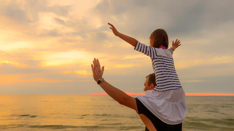 Child on dad`s shoulders on the background of the setting sun on a seaside beach royalty free stock images