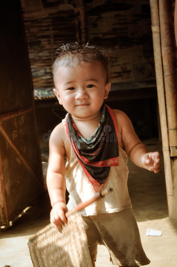 Child in Damak in Nepal. Damak, Nepal - circa May 2012: Small cute boy and holds wooden stick in his hand at Nepali refugee camp in Damak, Nepal. Documentary royalty free stock photo