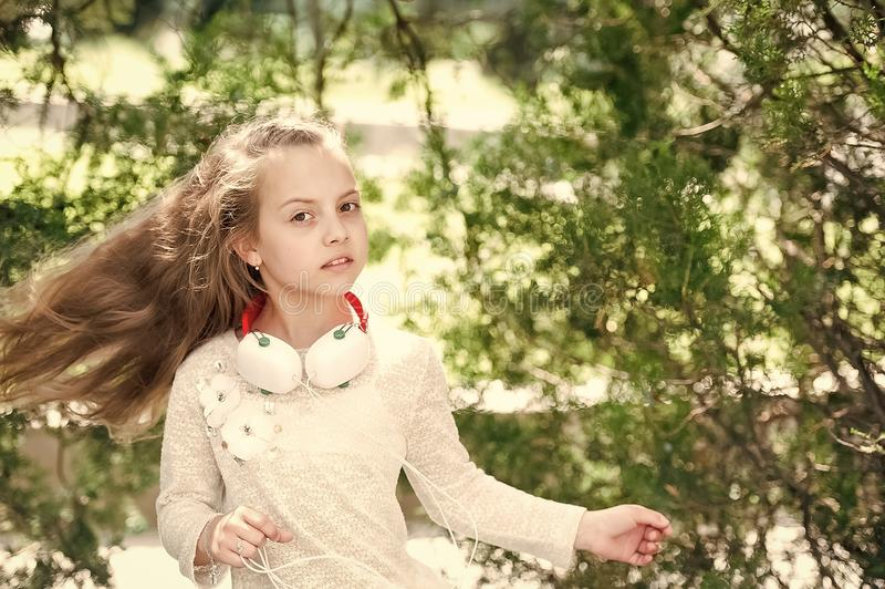 Child dance to music in summer park. Small girl enjoy music in headphones outdoor. Kid dancer with long flying hair. Melody sound and mp3. Summer fun and joy royalty free stock photos