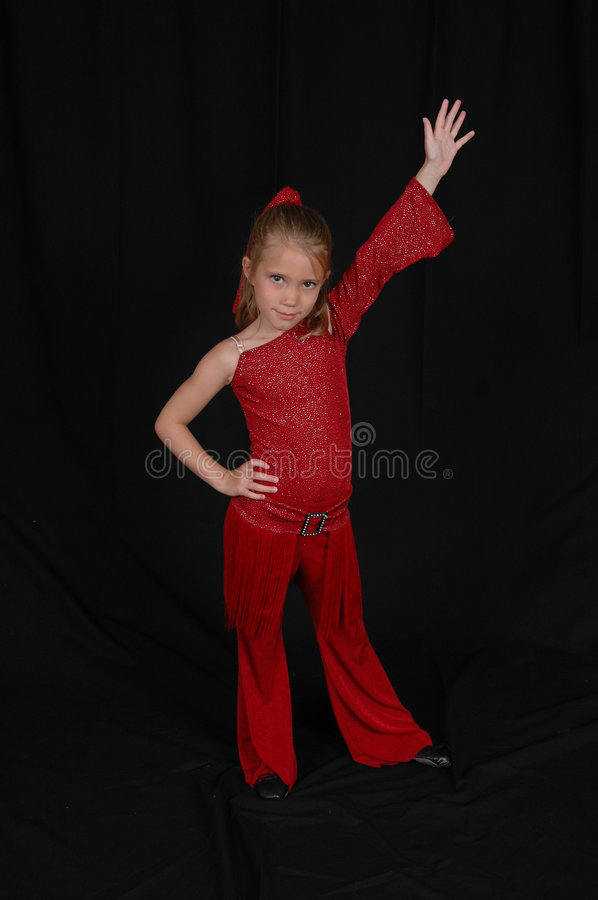 Child Dancer. Girl dancer in dance outfit striking a pose with one arm up. Beautiful Young blonde model royalty free stock photography