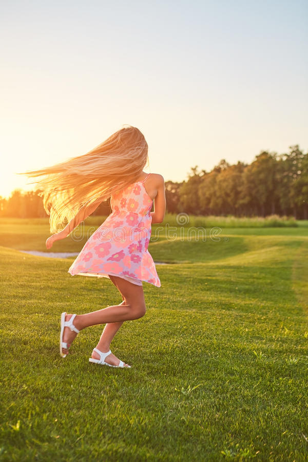 Child dancing on the grass. stock image