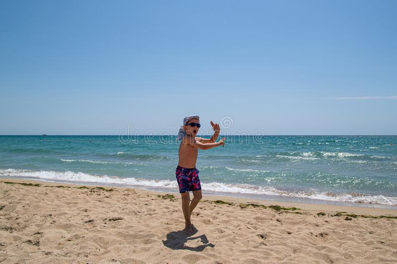 Child dancing and jumping on the beach stock photo
