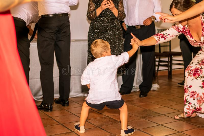 Child dancing with several adults in the celebration of a wedding, encouraging people. stock images