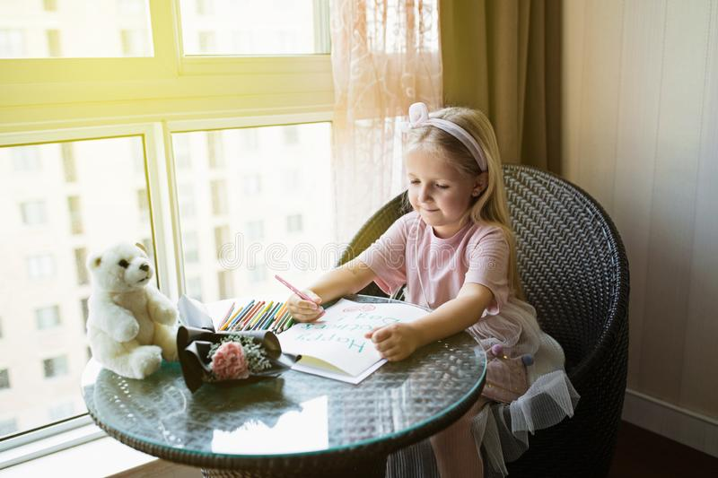 Child daughter painting postcard for mom. Girl sitting at home on table, next lying pink flower for mother. Mother day concept royalty free stock image