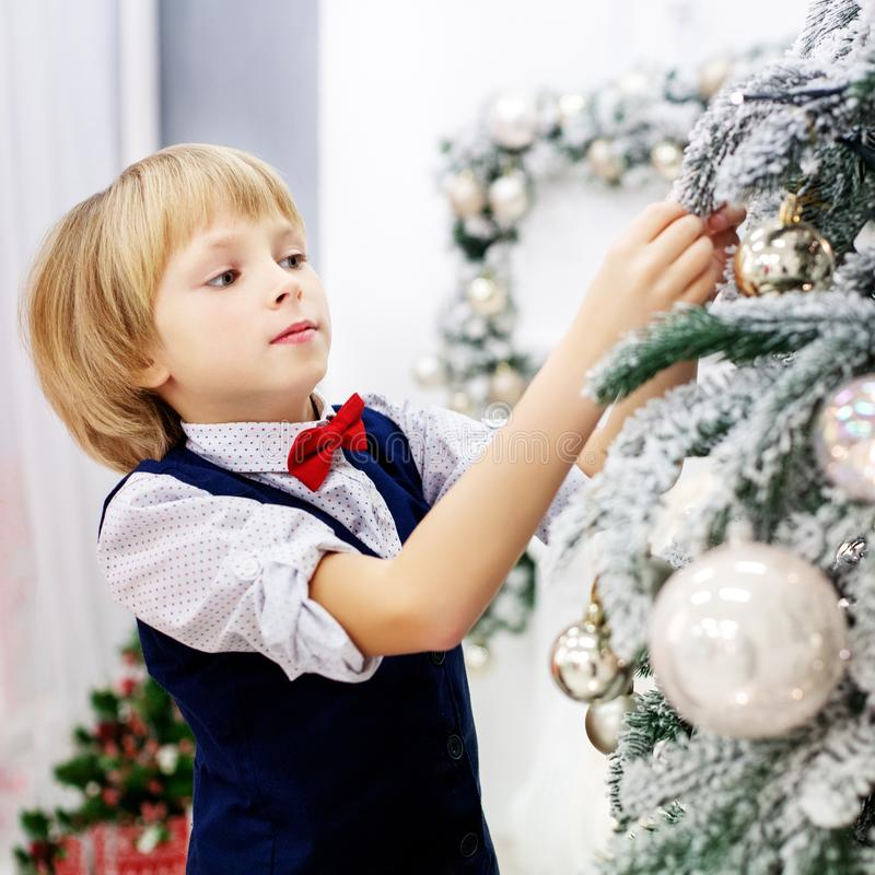 The child decorates a Christmas tree in the room. Concept winter stock photo