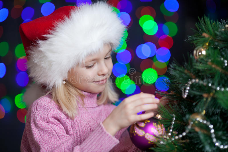 Child Decorating Christmas Tree On Bright Backdrop Stock Images